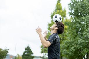 公園でサッカーをする若い男性の写真素材 [FYI04764247]