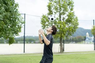 公園でサッカーをする若い男性の写真素材 [FYI04764248]