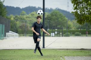 公園でサッカーをする若い男性の写真素材 [FYI04764249]