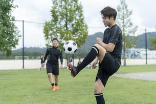 公園でサッカーをする若い男性の写真素材 [FYI04764250]