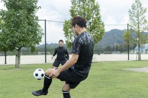 公園でサッカーをする若い男性の写真素材 [FYI04764251]
