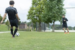公園でサッカーをする若い男性の写真素材 [FYI04764252]