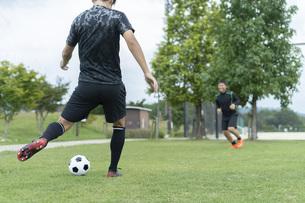 公園でサッカーをする若い男性の写真素材 [FYI04764253]