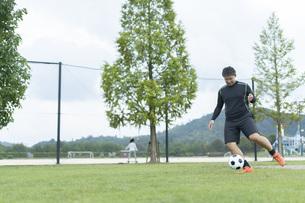 公園でサッカーをする若い男性の写真素材 [FYI04764254]