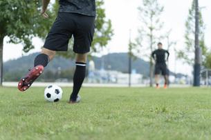 公園でサッカーをする若い男性の写真素材 [FYI04764255]