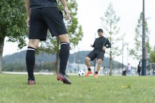 公園でサッカーをする若い男性の写真素材 [FYI04764256]