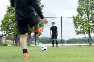 公園でサッカーをする若い男性の写真素材 [FYI04764257]
