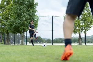 公園でサッカーをする若い男性の写真素材 [FYI04764258]