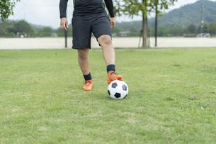 公園でサッカーをする若い男性の写真素材 [FYI04764259]