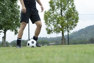 公園でサッカーをする若い男性の写真素材 [FYI04764260]