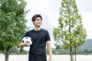 公園でサッカーをする若い男性の写真素材 [FYI04764261]