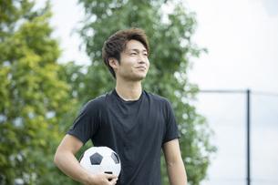 公園でサッカーをする若い男性の写真素材 [FYI04764263]