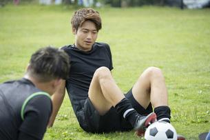 公園でサッカーをする若い男性の写真素材 [FYI04764265]
