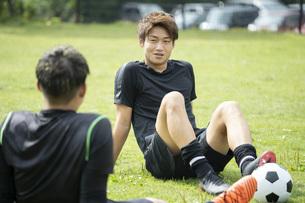 公園でサッカーをする若い男性の写真素材 [FYI04764266]