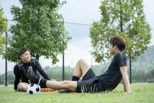 公園でサッカーをする若い男性の写真素材 [FYI04764267]