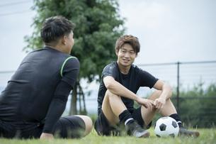 公園でサッカーをする若い男性の写真素材 [FYI04764268]