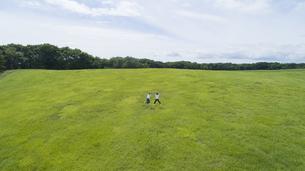 草原でジャンプをするカップルの写真素材 [FYI04764369]
