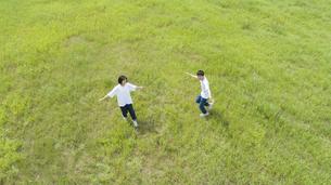 草原で遊ぶカップルの写真素材 [FYI04764371]