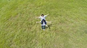 草原で肩車をするカップルの写真素材 [FYI04764372]