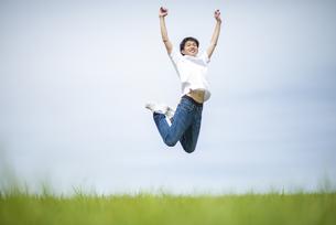 草原でジャンプする男性の写真素材 [FYI04764393]