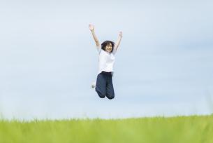 草原でジャンプする女性の写真素材 [FYI04764394]