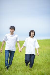 草原で手をつなぐカップルの写真素材 [FYI04764404]