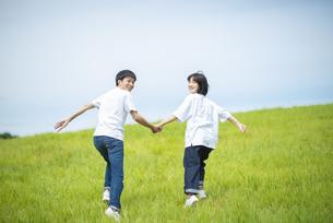 草原で手をつなぐカップルの写真素材 [FYI04764406]