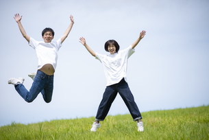 草原でジャンプをするカップルの写真素材 [FYI04764412]