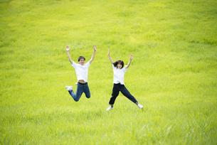 草原でジャンプをするカップルの写真素材 [FYI04764418]