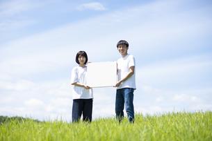 草原でホワイトボードを持つカップルの写真素材 [FYI04764435]
