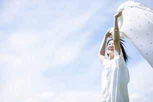 空の下で布を風になびかせる女性の写真素材 [FYI04764451]