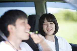 車の中で飴を食べさせる女性の写真素材 [FYI04764638]