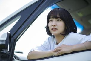 車の助手席から外を見る女性の写真素材 [FYI04764643]