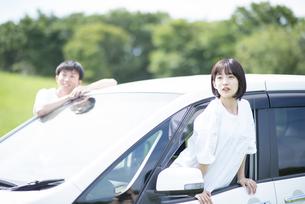 車の助手席から身を乗り出す女性の写真素材 [FYI04764647]