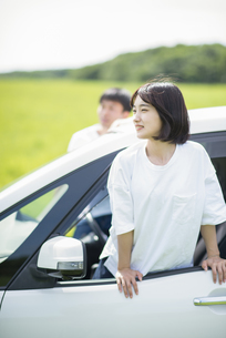 車の助手席から身を乗り出す女性の写真素材 [FYI04764648]