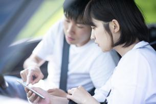 車内でスマホを見るカップルの写真素材 [FYI04764649]