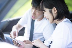 車内でスマホを見るカップルの写真素材 [FYI04764650]