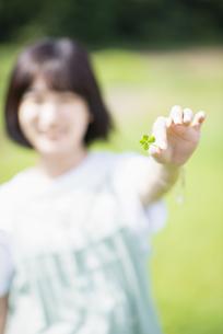 四つ葉のクローバーを持つ女性の手元の写真素材 [FYI04764658]