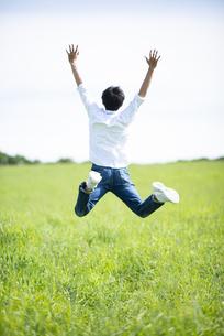 草原でジャンプをする男性の後ろ姿の写真素材 [FYI04764661]