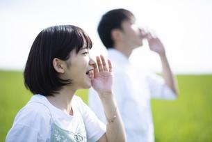 草原で叫ぶカップルの横顔の写真素材 [FYI04764678]