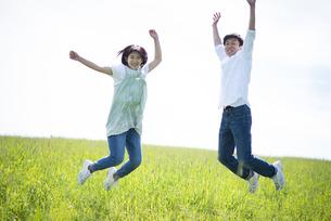 草原でジャンプをするカップルの写真素材 [FYI04764698]