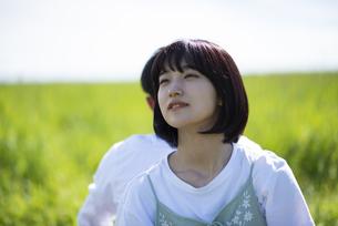 草原で遠くを見つめる女性の写真素材 [FYI04764712]