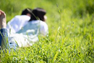 草原で寝転ぶカップルの写真素材 [FYI04764722]