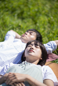 草原で寝転ぶカップルの写真素材 [FYI04764726]
