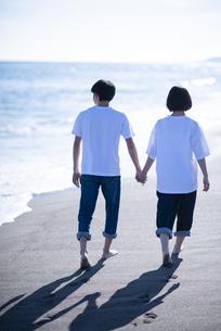 海辺で手をつなぐカップルの後ろ姿の写真素材 [FYI04764734]