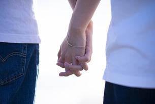 海辺で手をつなぐカップルの手元の写真素材 [FYI04764741]