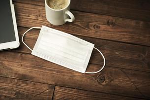 机の上にマスクとコーヒーの写真素材 [FYI04765645]