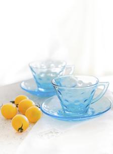 白いテーブルの上に置かれたガラス製の青いコーヒーカップと黄色のミニトマトの写真素材 [FYI04765918]