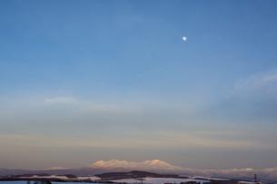 夕映えの雪山と月の写真素材 [FYI04766043]