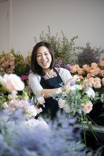 花屋で仕事をしながら笑っている女性の写真素材 [FYI04766109]